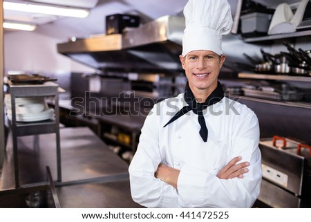 Portrait of confident chef standing in kitchen with hands crossed