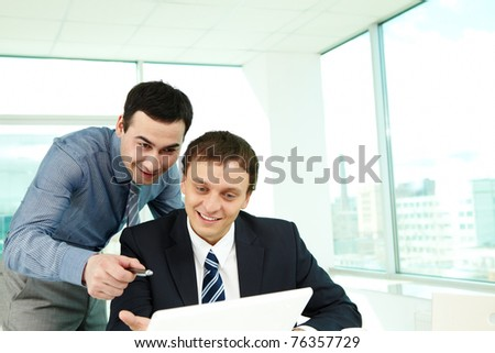 Portrait of confident colleagues looking at laptop screen in office - stock photo
