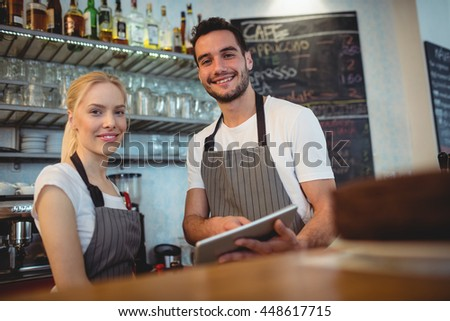 Portrait of confident colleagues with digital tablet standing at cafe - stock photo