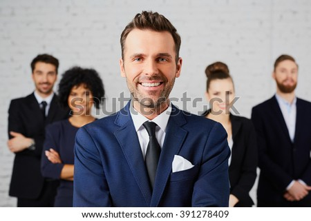 Portrait of confident company leader with business partners behind - stock photo