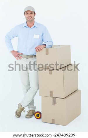 Portrait of confident delivery man leaning on stacked cardboard boxes over white background - stock photo