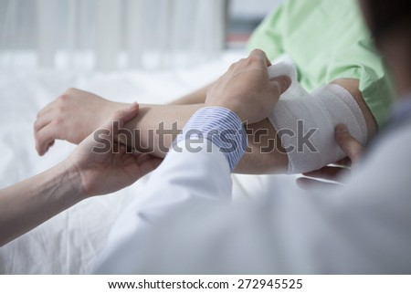 Portrait of confident doctor giving first aid to male patient in hospital  - stock photo