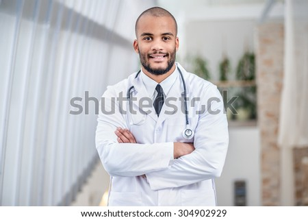Portrait of confident doctor. Smiling doctor folded his arms and looking at the camera - stock photo