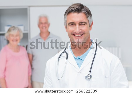Portrait of confident doctor smiling with senior couple in background at clinic - stock photo