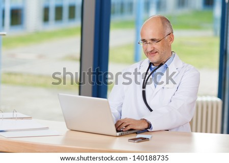 Portrait of confident doctor with hand on chin and laptop on desk in clinic - stock photo