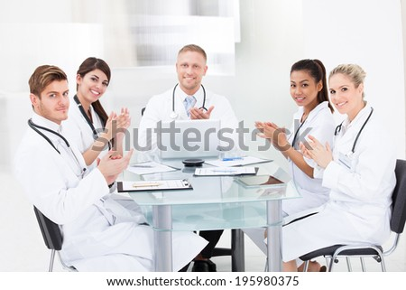 Portrait of confident doctors applauding while sitting at desk in clinic - stock photo