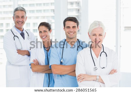 Portrait of confident doctors in row at medical office - stock photo