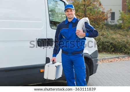 Portrait of confident electrician with cable coil and toolbox standing outside truck - stock photo
