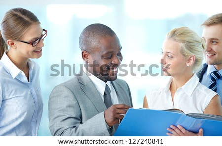 Portrait of confident employees discussing document at meeting - stock photo