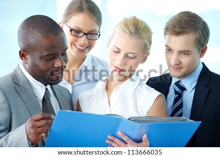 Portrait of confident employees looking at document at meeting
