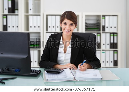 Portrait of confident female accountant writing on documents at desk in office - stock photo