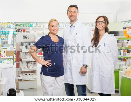 Portrait of confident female assistant with pharmacists standing in pharmacy - stock photo
