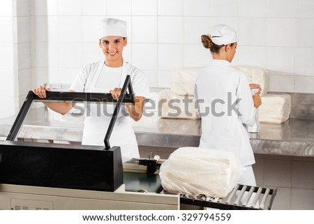 Portrait of confident female baker using vacuum seal machine while coworker working in bakery - stock photo