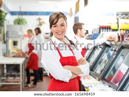 Portrait of confident female butcher standing arms crossed with colleagues in background - stock photo