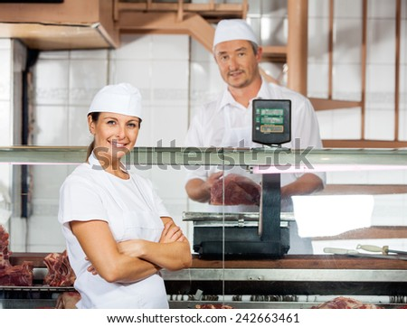 Portrait of confident female butcher with male colleague weighing meat at shop - stock photo