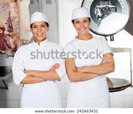 Portrait of confident female butchers smiling in butchery - stock photo