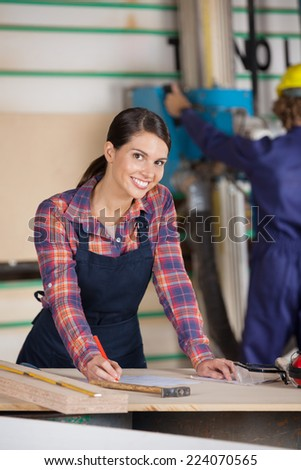 Portrait of confident female carpenter writing on document in workshop - stock photo