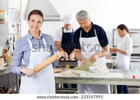 Portrait of confident female chef holding rolling pin while colleagues preparing pasta at commercial kitchen - stock photo