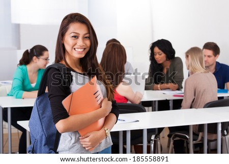 Portrait of confident female college student carrying backpack with classmates in background - stock photo