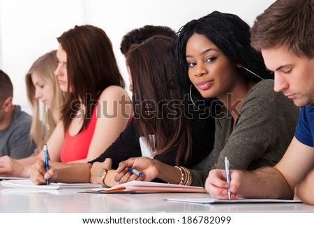 Portrait of confident female college student sitting with classmates writing at desk - stock photo