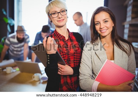 Portrait of confident female coworkers with colleagues in background at creative office - stock photo