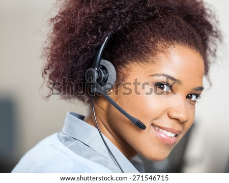 Portrait of confident female customer service agent wearing headset at desk in office - stock photo