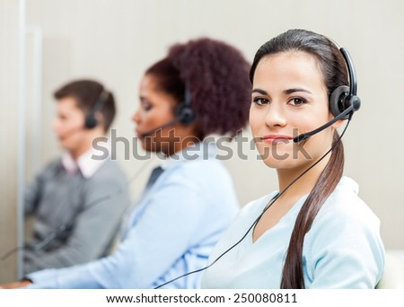 Portrait of confident female customer service representative with colleagues in background at office - stock photo