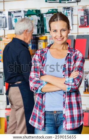 Portrait of confident female customer with arms crossed standing against worker in hardware store - stock photo