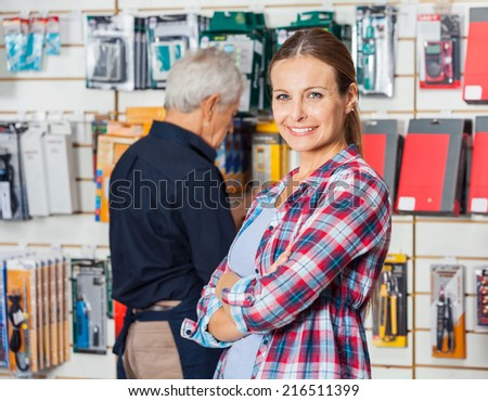Portrait of confident female customer with hands folded standing against worker in hardware store - stock photo