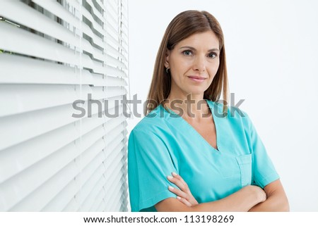 Portrait of confident female dentist standing with arms crossed in clinic - stock photo
