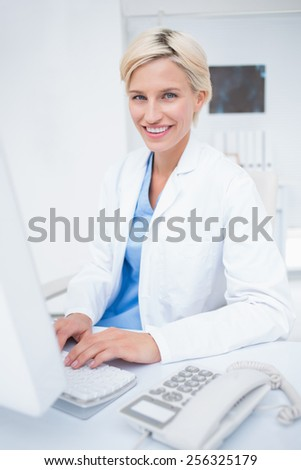 Portrait of confident female doctor using computer in clinic - stock photo