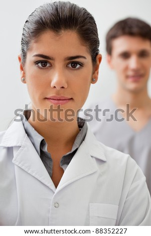 Portrait of confident female doctor with practitioner standing in background - stock photo