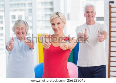 Portrait of confident female instructor with senior couple showing thumbs up in gym - stock photo