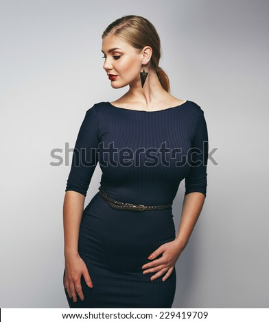 Portrait of confident female model posing against grey background. Plus size young caucasian woman. - stock photo