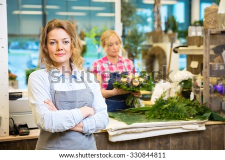 Portrait of confident female owner with worker in background at flower shop - stock photo