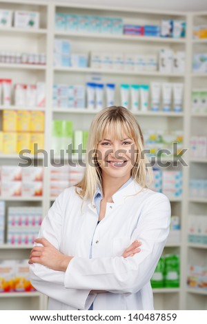 Portrait of confident female pharmacist with arms crossed standing in pharmacy - stock photo