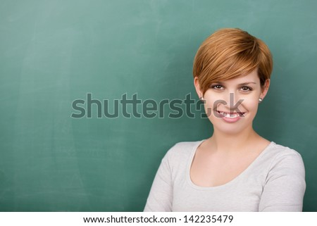 Portrait of confident female professor smiling against chalkboard - stock photo