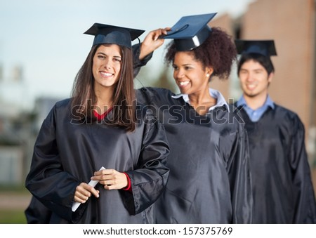 Portrait of confident female student holding certificate with friends standing in background on college campus