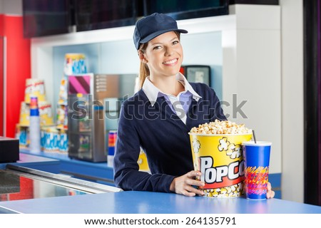Portrait of confident female worker with popcorn and drink standing at concession stand in cinema - stock photo