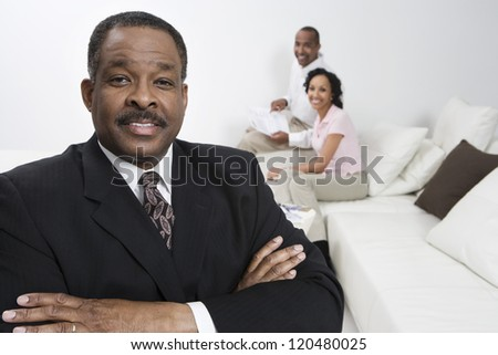 Portrait of confident financial adviser with happy couple in background