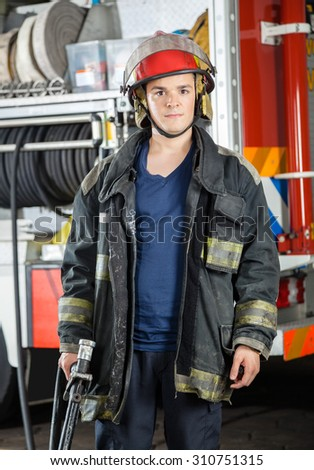 Portrait of confident firefighter holding hose against truck at fire station - stock photo