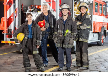 Portrait Of Confident Firefighters Standing Against Truck - stock photo