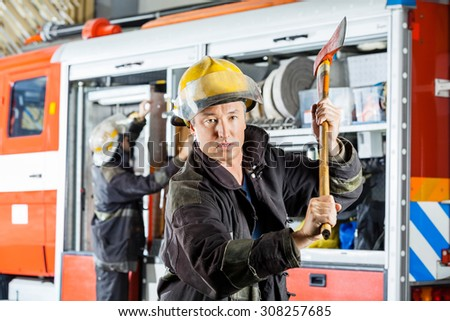 Portrait of confident fireman holding axe while standing against truck at fire station