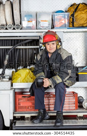 Portrait of confident fireman holding coffee mug while sitting in truck at fire station - stock photo