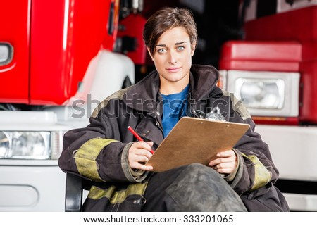 Portrait of confident firewoman holding clipboard while sitting against trucks at fire station - stock photo