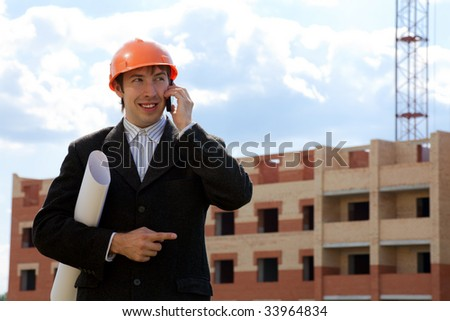 Portrait of confident foreman calling by the phone and holding document