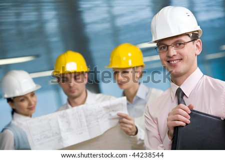 Portrait of confident foreman in helmet and eyeglasses looking at camera - stock photo