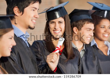 Portrait of confident graduate student holding diploma while standing with friends at university - stock photo