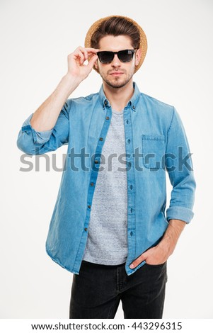 Portrait of confident handsome young man in hant and sunglasses over white background - stock photo