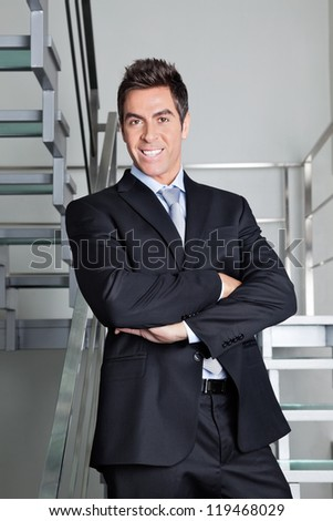 Portrait of confident happy young businessman standing on stairs - stock photo